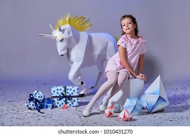 Fashion kid. Designer collection. White big unicorn origami made of paper. Girl in beautiful pink dress. Studio shot.
