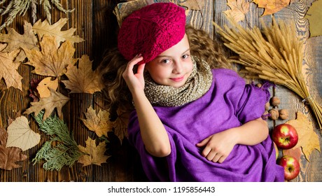Fashion kid girl wear knitted hat beret and scarf. Autumn fashion accessories concept. Fashion trend fall season. Child lay wooden background fallen leaves top view. Knitted accessory fashion detail.