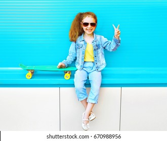 Fashion kid smiling little girl with skateboard in the city on a colorful blue background