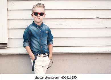 Fashion kid summer in the city stands on a white wall. Trendy boy in sunglasses standing on the street at sunset.