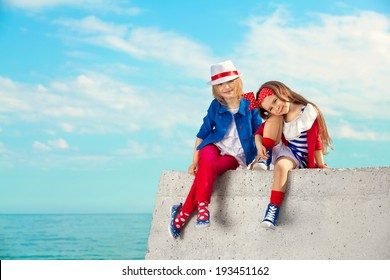 Fashion kids resting on the sea . Vacation, friendship, fashionable concept.