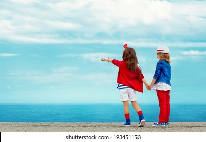 Fashion kids stands on stone breakwater and points to the sea. Vacation, friendship, fashionable concept.
