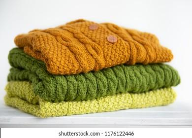Fashion knitted handmade cardigans (jackets) folded and lying on a shelf  isolated on white background/ Close up/ Knitting/ Hobby