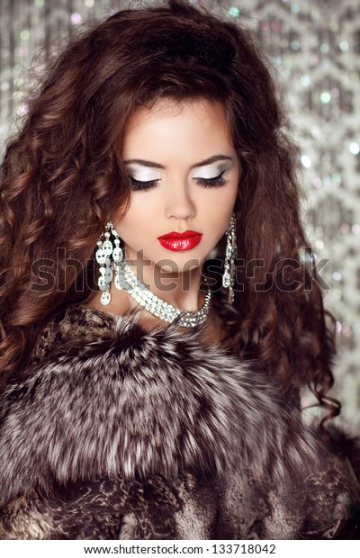 Fashion lady, Beautiful woman in fur coat posing in luxury brilliant jewelry at royal apartment interior.