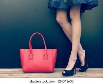 Fashion leggy girl in a beautiful high-heeled shoes in short denim dress summer posing near the dark wall. Close-up. Warm color