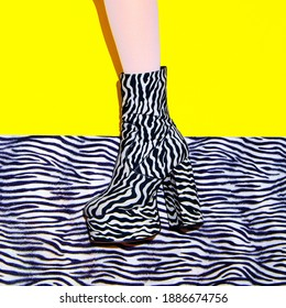 Fashion legs in heel party zebra print boots on yellow minimal background. Animal texture design. Stylish tropical concept