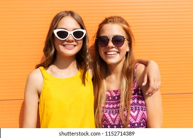 fashion, leisure and people concept - smiling teenage girls in summer clothes hugging outdoors