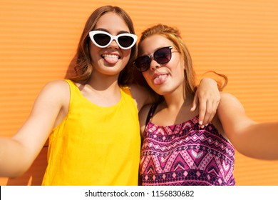 fashion, leisure and people concept - smiling teenage girls taking selfie outdoors in summer