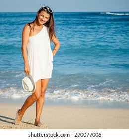 Fashion Lifestyle, Beautiful brunette girl in the sunglasses and white hat on the beach at the day time. Travel and Vacation.