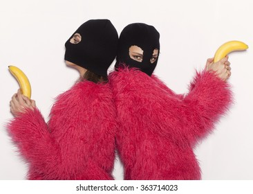 fashion lifestyle portrait of pretty best friends girls in bandit masks,pink fur,having fun and make crazy faces.Two sisters posing party.Hipster.Swag style.Calling with bananas.OMG.LOL.Hipster.WTF.