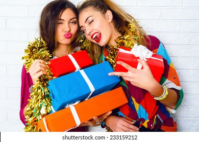 Fashion lifestyle portrait of two girls friends holding birthday bright presents, wearing trendy clothes and sparkled tinsel. Going crazy, and making funny faces.