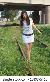 Fashion lifestyle portrait of young pretty woman in white costume with skirt outdoors