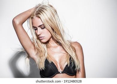 Mode- und Dessous-Konzept - schönes blondes Damenporträt in sexy BH und Pantoletten auf weißem Hintergrund. Frauen, die Unterwäsche tragen, stellen sich in hellem Licht.
