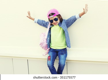 Fashion little girl child wearing a sunglasses and baseball cap in city over white background