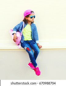 Fashion little girl child wearing a baseball cap and backpack in the city on a white background