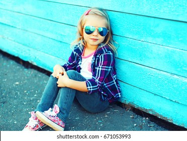 Fashion little girl child wearing a sunglasses and checkered shirt sitting in the city