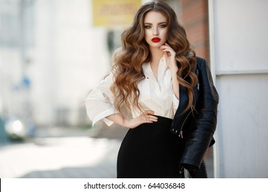 Fashion long hair woman with red lips wear trendy white shirt and black skirt and hold leather jacket at city street. Stylish young model girl in elegant clothes outdoors. Lady with bright makeup.