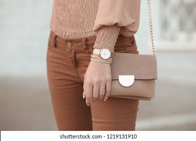 Fashion look autumn woman outfit. Stylish women's beige handbag. Closeup of luxury watch and feminine accessories in pastel colored. Cute beige ladies purse bag.