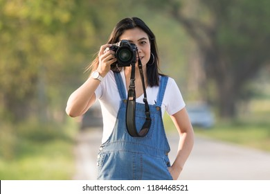 Fashion look, pretty cool young woman model with  dslr digital camera in hand, she hapy in outdoors over nature green background