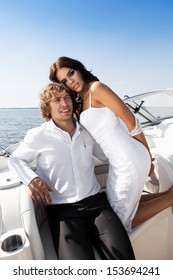 Fashion lovely beautiful couple posing on the boat in open sea in summer. Young man and sensual brunette outdoor portrait in classic dress near the ocean. Outdoors, lifestyle.