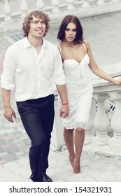 Fashion lovely couple walking in the old part of town. Young man and sensual brunette outdoor portrait in classic dress. Outdoors, lifestyle.