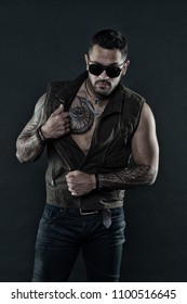Fashion macho with tattoo on chest and arms. Fashion style and trend. Tattoo model with beard on unshaven face. Tattooed man with biceps and triceps. Bearded man in trendy sunglasses, vintage filter.