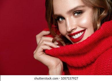 Fashion And Makeup. Beautiful Smiling Woman With Red Lips In Red Pullover Sweater On Red Background. High Quality