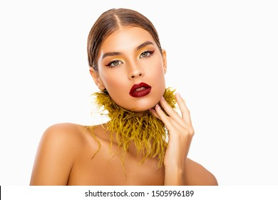 Fashion make-up. Bright Caucasian Woman. Style Makeup model with Red Lips and eyeliner, mustard Eyeshadow and feathers on the neck. Isolated. Beautiful Portrait Glamor Woman. burgundy eyeliner. arrows