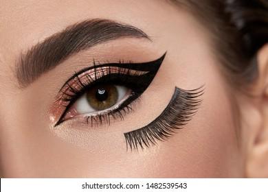 fashion make-up closeup with eyeliner and false eyelashes under eye, make-up art with cat eyes, glamorous evening style
