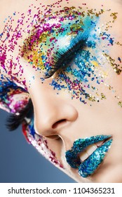 Fashion makeup. Close-up of a young woman with glitter make-up on a dark background