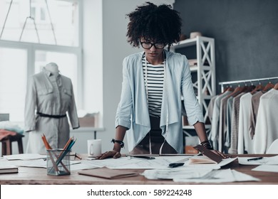 Fashion in the making. Beautiful young African woman looking at sketches while leaning on the desk in workshop with clothes hanging in the background