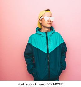 fashion male model standing in the turquoise jacket, cap and sunglasses. clothing in the style of the 90s and the rave. minimal.