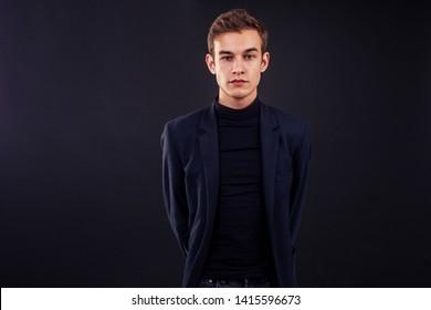 fashion man asymmetric facial features ears in suit black background studio