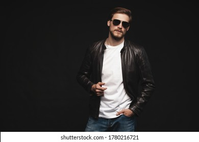 Fashion man, Handsome beauty male model portrait wear sunglasses and leather jacket, young guy over black background.