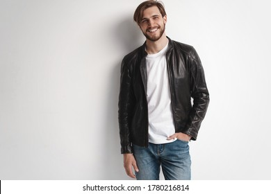 Fashion man, Handsome serious beauty male model portrait wear leather jacket, young guy over white background.