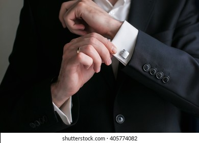 fashion man looking at his cufflinks while fixing them