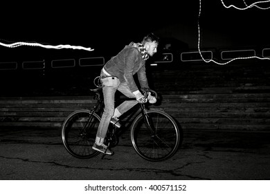 Fashion man on the fixed gear bike rides around the city at night. Black and white