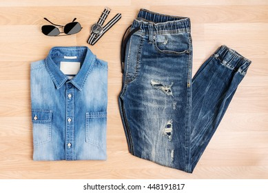 Fashion men and accessories new trendy blue jeans jog pants shirt sunglasses and watch on wooden table, Top view
