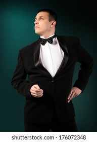 Fashion Men in Classic Tuxedo on dark abstract background