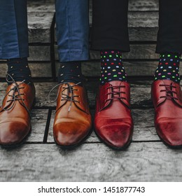 Fashion men footwear. Two guys wearing leather red shoes and colorful socks sitting on wooden stairs.