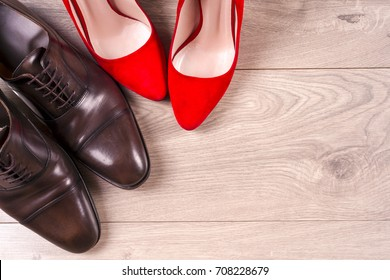 Fashion. men's shoes and red high heel women's shoes on wooden background. Top view. Copy space for text.