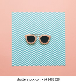 fashion minimal concept of pink sunglasses on geometric paper background. flat lay.
