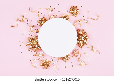 Fashion mockup with golden bows, serpentine and star confetti on pink pastel table top view. Flat lay card for birthday, christmas or wedding.