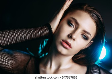 Fashion model beautiful girl in fashionable clothes in ultraviolet light, showing different poses. Beauty body and face. Photos shot in studio. Advertising Space