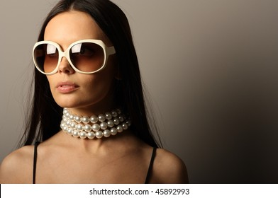 Fashion model with big white sunglasses and pearls necklace.