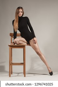 fashion model in black body on chair isolated on gray studio background