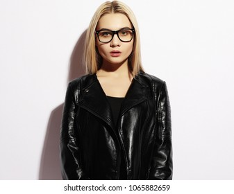 Fashion model in black clothing. Leather jacket and pants, blank t-shirt and sunglasses. Street urban minimalist style.Studio shoot.