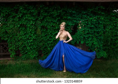 Fashion model blonde woman with curly hairdo up, posing sexy, wearing adjusting long blue golden evening dress standing in a green garden on background, looking to side thoughtful hand on cheek.