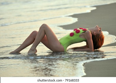 Fashion model in custom design lime color swimwear with flowers lying down on the sunset beach in Reese Park, NY