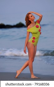 Fashion model in custom design lime color swimwear with flowers posing on the sunset beach